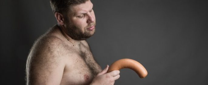Sad-man-looks-at-the-sausage-in-his-hand-805x516