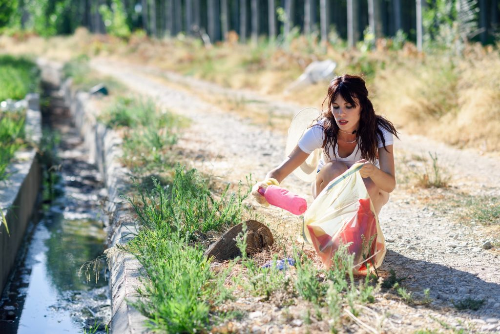 Young woman hand collecting garbage of the grass in the countryside