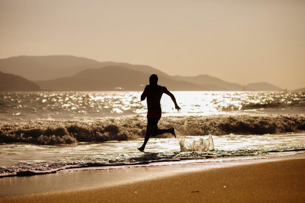 silhouette  freedom man run into the sea on sunrise
