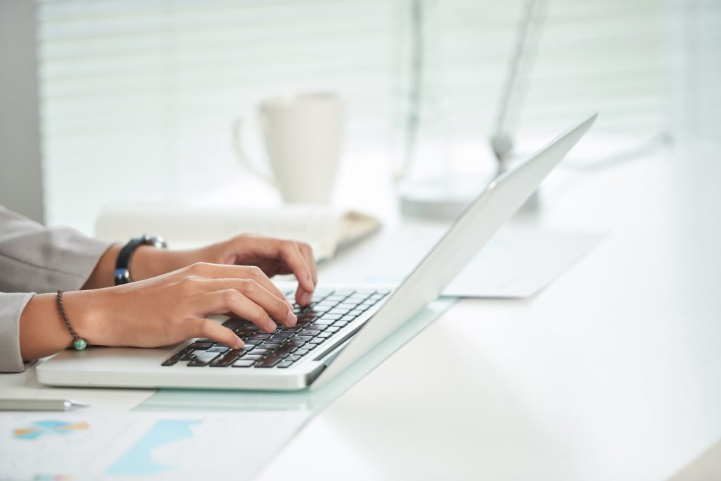 Hands of business woman working on laptop in her office