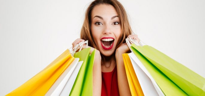 Close up portrait of a happy cheerful woman in red dress holding colorful shopping bags isolated on a white background